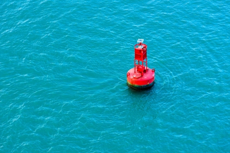 buoys: A bright red buoy floating in a blue ocean