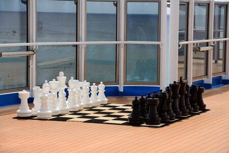outwit: Big chess pieces on board - outside  Stock Photo