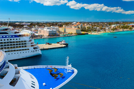 vacationing: A view of a large cruise ship docked along the waterfront of Nassau, Bahamas