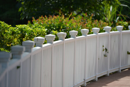 lowers: White picket fence with green grass background and lowers in background