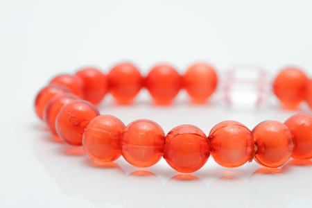 Close-up of red coral beads on white background  photo