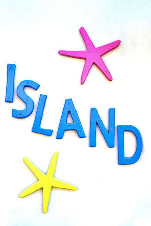 Island sing with pink and yellow star fish on white photo