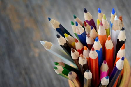 blue pen: Colorful pencils in ceramic boot on wood background