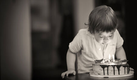 Cute young blond three year old girl with decorative birthday cake