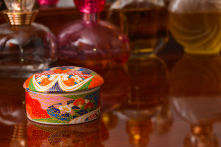 Asian ceramic jewelry box sitting on a varnished wooden cupboard photo