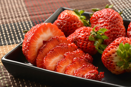 Single well formed strawberry with leaves in group of strawberries  photo