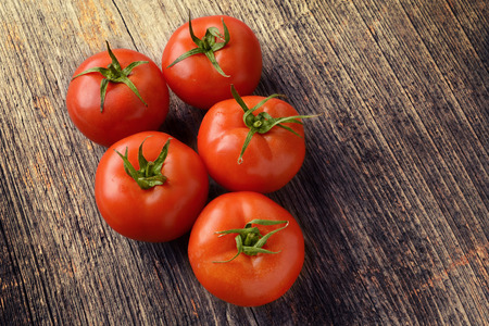 Fresh tomatoes placed on a wooden texture