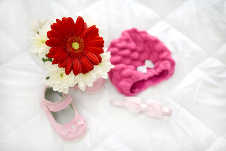 Gerbera pink baby shoes and headpiece pink in natural light Stock Photo