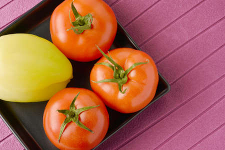 Fresh tomatoes and bell peppers arranged on a black ceramic plate Stock Photo