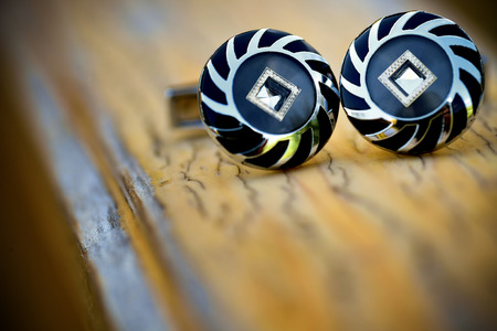 cufflink: Special cufflinks sitting on a old wooden surface
