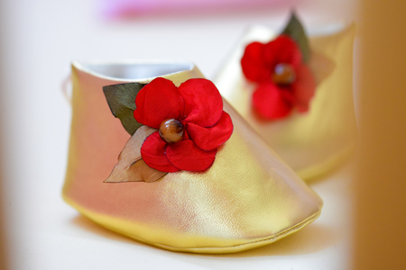 copper coated: Shoes newborn gold with a red flower on the side