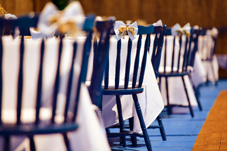 mo�o blanco: Blue wooden chairs with white bow during wedding day