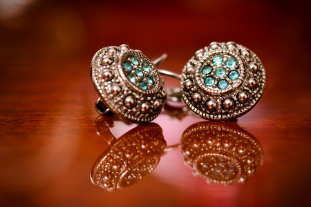 silver jewellery: Silver earrings with green stones on a varnished wooden background