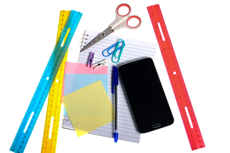 Variety of stationery items and a smartphone isolated on white background photo
