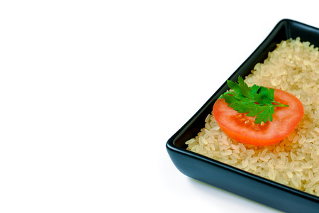tomato slice: Isolated plate with uncooked rice and tomato slice