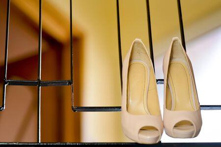 stilleto: White stilleto bridal shoes hanging Stock Photo