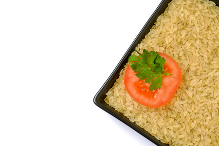 tomato slice: Plate with uncooked rice and tomato slice