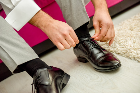 shoe strings: Man tying shoelaces shoes in natural light Stock Photo