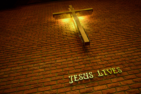 wrote: Cross and wrote Jesus Lives on a brick wall