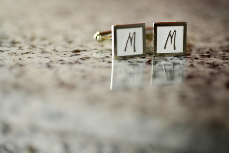 cufflinks: Silver cufflinks with white stone and M sign