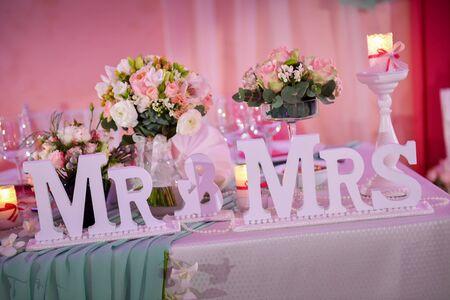 mrs: mesa de boda hermosa con el Sr. y Sra. en la luz natural