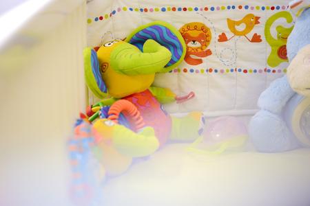 baby crib: Toy elephant sat in a baby crib Stock Photo