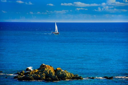 thomas stone: Sailing boat on ocean with big rock on foreground