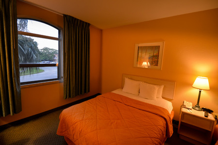 queen bed: Room interior with bed, lamp and view outside