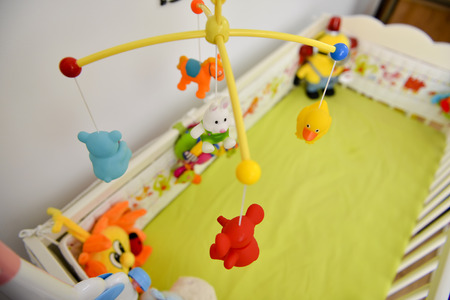 cot: Baby cot with colorful toys hanging Stock Photo