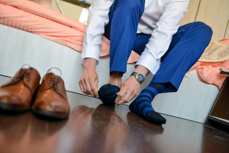 Man who put his socks with shoes in front of him