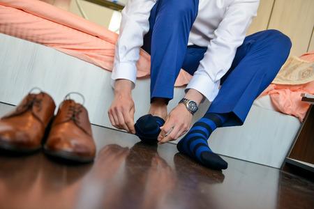 Hombre que puso los calcetines con los zapatos delante de él