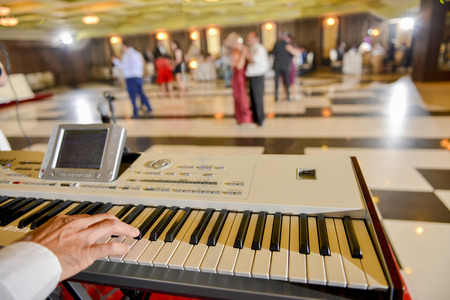 electronic piano: Man who playing on a electronic piano in restaurant Stock Photo