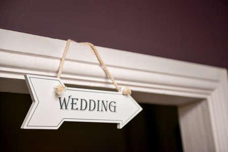 hanged: Wedding sign hanged on top of door