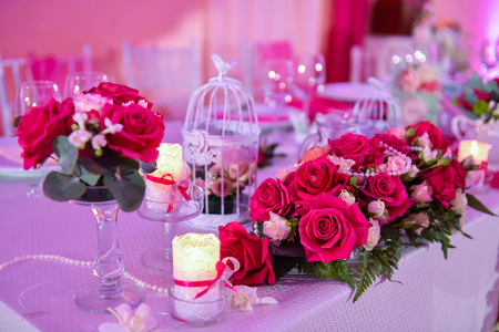 arrangment: Roses on a wedding table with candles