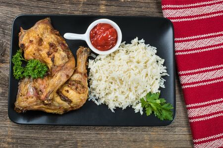 muslos: Grilled chicken thighs with rice on the table with cutlery