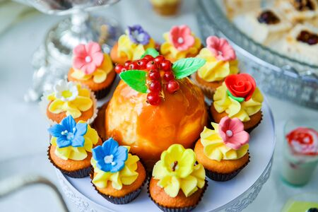 Muffins decorated with cream flowers on the table