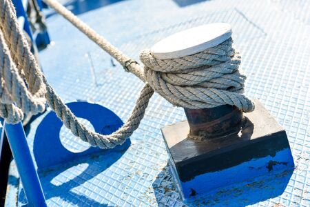 Rope tied to steel bollard on deck in natural light Stock Photo