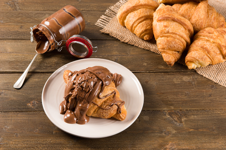 Croissant with chocolate cream on the table in natural light