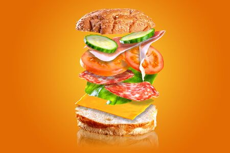 Flying tasty sandwich ingredients isolated on orange