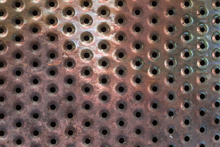 metal grate: Holes in piece of metal worn with fire