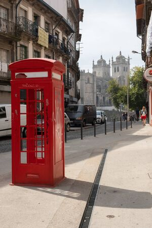 Porto, Portugal - September 16, 2018: Red telephone booth of Rua Ch? in the city of Porto and in the background we can see the Cathedral of Porto, Portugal Sajtókép
