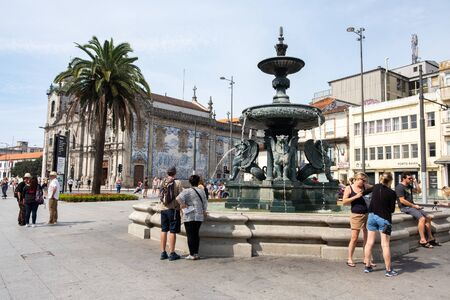 Porto, Portugal - September 16, 2018: Fountain of the Lions, in Pra?a de Gomes Teixeira, in the background the Church of Our Lady of Carmo Porto, Portugal