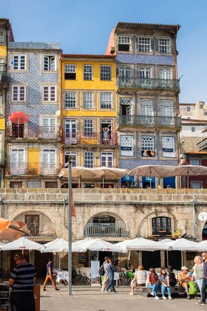 Porto, Portugal - September 16, 2018 : Everyday life in the city tourists passing people in the windows of the colorful houses Porto, Portugal