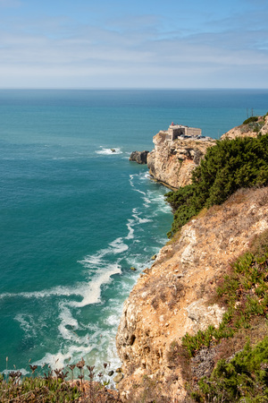 Nazare, Portugal - September 20, 2018 : On the cliffs of yellow stone the Lighthouse of the Nazare, S. Miguel Archangel Fort Nazare, Portugal