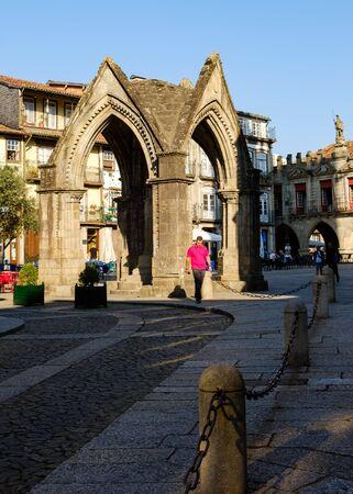 Guimaraes, Portugal - September 26, 2018 : The Largo do Oliveira as the beautiful Monument Padrao do Salado always frequented by tourists Guimaraes,Portugal