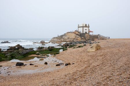 Vila Nova de Gaia, Portugal - September 30, 2018 : Empty tide reveals the mossy rocks near the chapel, Porto district, Portugal Sajtókép