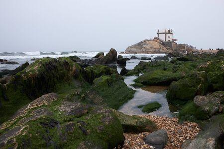 Vila Nova de Gaia, Portugal - September 30, 2018 : Empty tide reveals the mossy rocks near the chapel, Porto district , Portugal