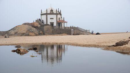 Vila Nova de Gaia, Portugal - September 30, 2018 : Pilgrims visit the chapel on foggy days by the sea Porto district , Portugal