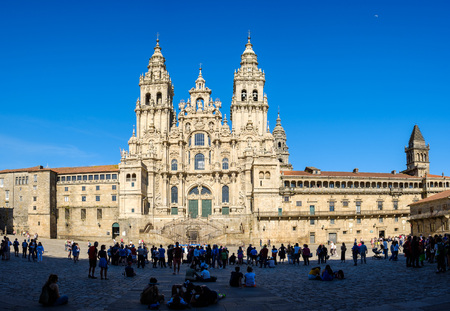 Santiago de Compostela , Spain - May 12, 2019: Tourists and pilgrims roam the streets where magnificent buildings are situated in the historic Spanish city, Santiago de Compostela, Spain.