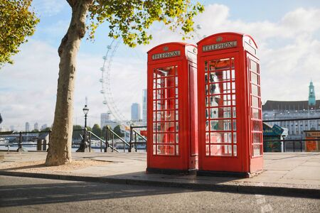 Two red telephone booths resting on an empty street in the early morning hours on the River Thames. Foto de archivo